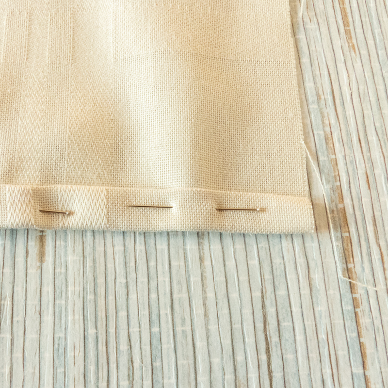 mostrar cómo se hace el dobladillo de un mantel o una servilleta de tela