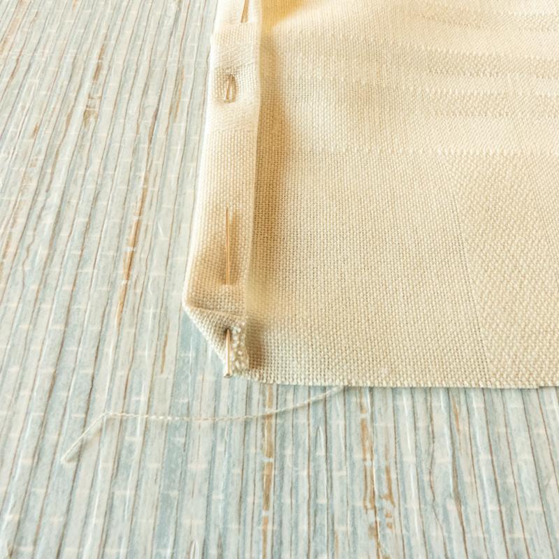 mostrar cómo se hace el dobladillo de un mantel o servilleta de tela