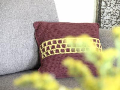 Cojin de ganchillo en un sofá